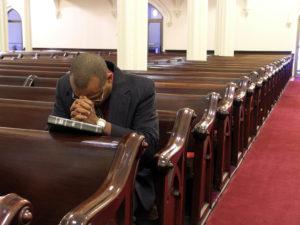 African-American man praying alone.